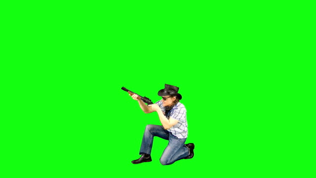 Cool confident cowboy in a hat and in sunglasses squats, charges his carbine, takes aim, shoots. Videoclip on a green screen. macho stock videos & royalty-free footage