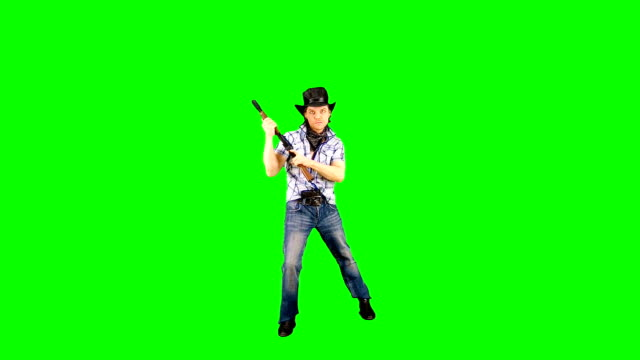 Cool confident cowboy in a hat charges a carbine and shoots. Videoclip on a green screen. macho stock videos & royalty-free footage