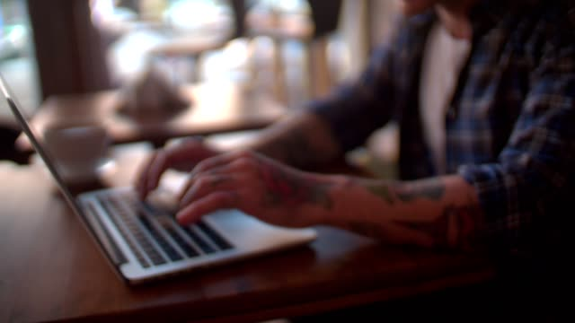 Cool enterpreneur working on his laptop in coffee shop Close up of young man hands typing and chatting online at cafeteria. Hip youngster searching online at cafe tattoo stock videos & royalty-free footage