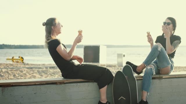 cool female friends having ice cream in the sunset - tatuaż filmów i materiałów b-roll