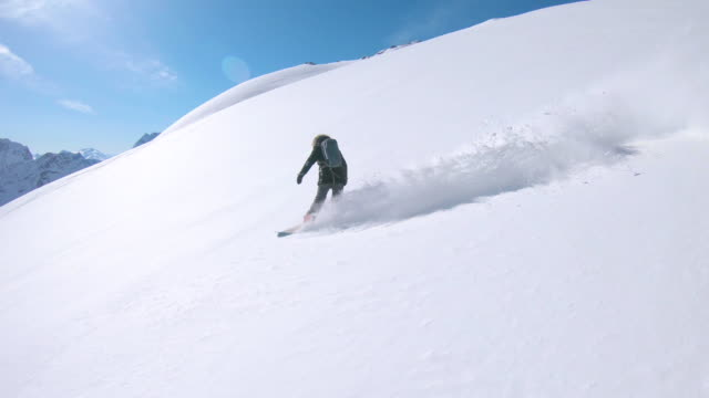 cool female tourist heliboarding down the scenic mountain covered in fresh snow. - snowboarding video stock e b–roll