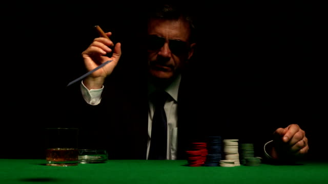 Cool gambler playing poker in sunglasses video