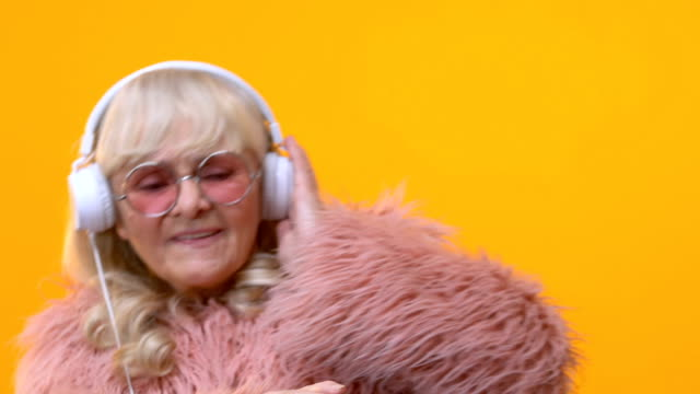 Cool grandmother in white headphones moving to music, pretending be dj, fun
