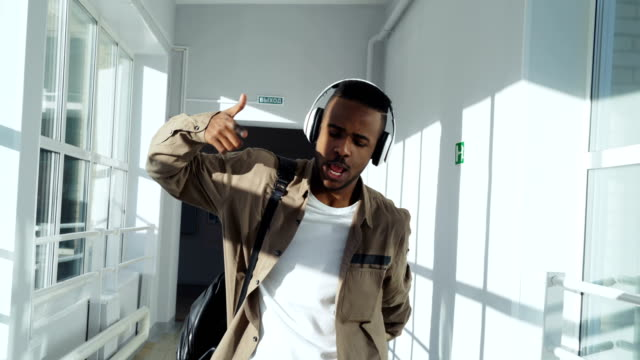 cool happy african american guy dancing listening to music in headphones walking and passing by group of classmates making thumbs up to him - hip hop video stock e b–roll