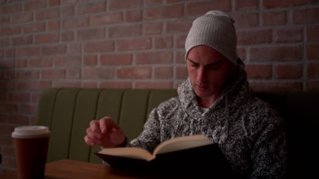 Cool hipster reading a book in modern coffee shop video