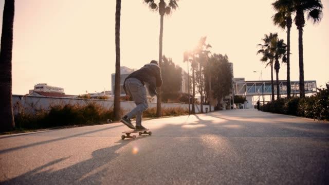 stockvideo's en b-roll-footage met coole hipster teenage skateboarder doen longboarding in de stad - street style