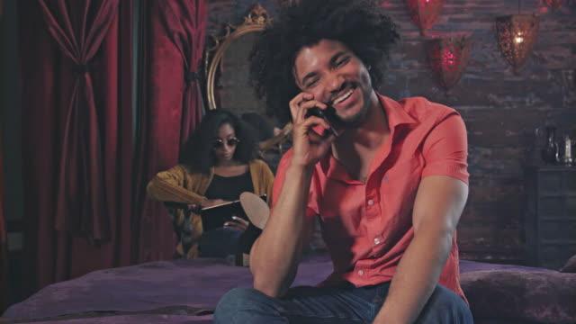 vídeos de stock, filmes e b-roll de cool hipster jovem tem conversa positiva - afro americano