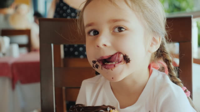 vídeos de stock e filmes b-roll de a cool little girl is eating a sweet bun, her face is smeared with chocolate - chocolate