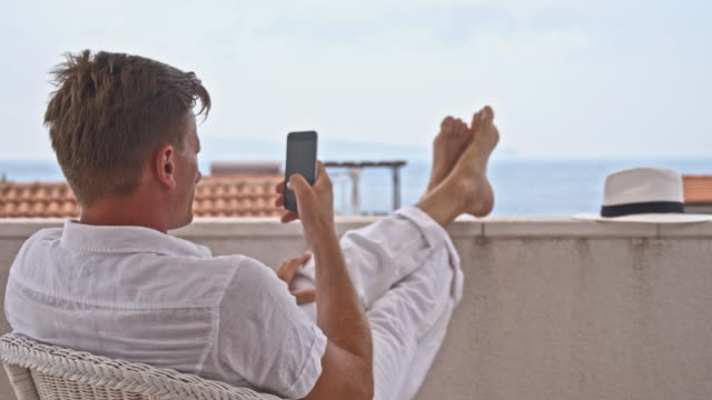 DS Cool man using smartphone on the balcony video