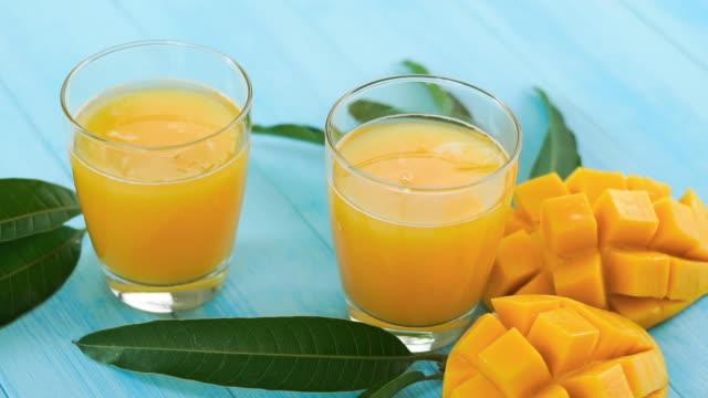 cool mango juice drinkar i glasen bredvid bitar av mango frukt och gröna blad - blue yellow bildbanksvideor och videomaterial från bakom kulisserna