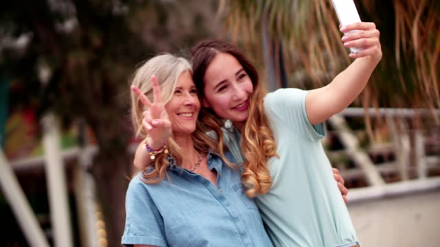 Cool mother and daughter taking selfies in the city video
