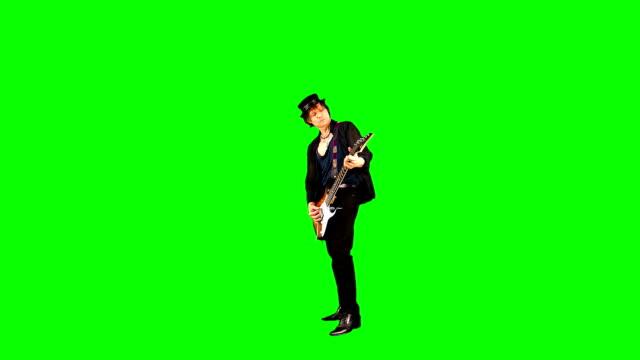 cool rockgitarrist i en hatt spelar elgitarr på chroma nyckel. musiker uppträder på en grön bakgrund. - gitarrist bildbanksvideor och videomaterial från bakom kulisserna