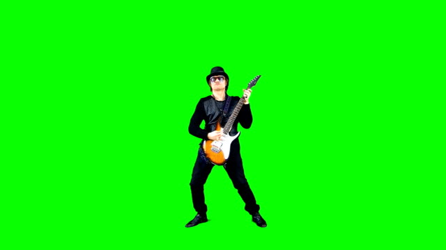 cool rock guitarist in a hat playing the electric guitar on the chroma key. musician performing  on a green background. - гитара стоковые видео и кадры b-roll