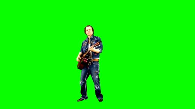 cool rockgitarrist i en jeans kostym spelar akustisk gitarr på chroma nyckel. musiker uppträder på en grön bakgrund. - gitarrist bildbanksvideor och videomaterial från bakom kulisserna