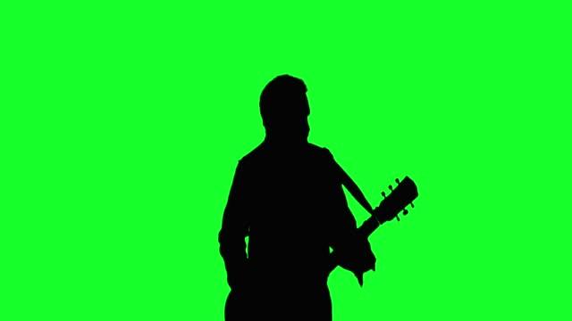 vídeos de stock, filmes e b-roll de guitarrista de rock legal de chapéu tocando o violão na tela verde. - música acústica