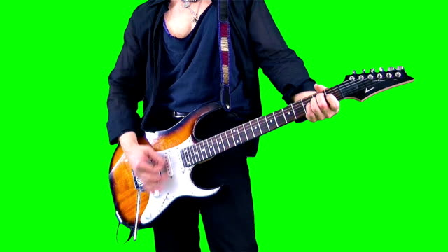cool rock guitarist playing the electric guitar on the chroma key. musician performing  on a green background. - гитара стоковые видео и кадры b-roll