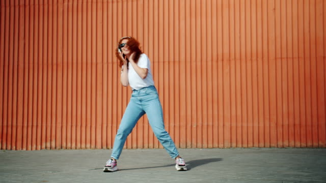 Cool student girl dancing outdoors wearing headphones and sunglasses Cool student girl is dancing outdoors wearing headphones and sunglasses enjoying music through modern wireless device. Lifestyle and technology concept. redhead stock videos & royalty-free footage