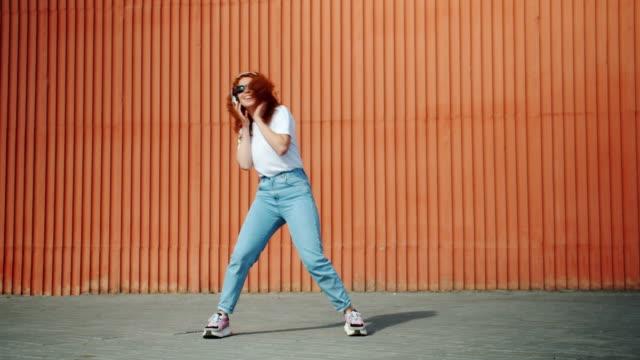cool student tjej dansar utomhus bär hörlurar och solglasögon - rött hår bildbanksvideor och videomaterial från bakom kulisserna