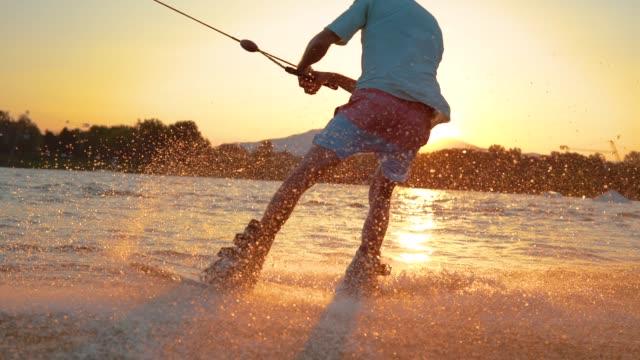 slow motion: cooler surferdude macht 180 ollie beim wakeboarden am sonntagabend - sprung wassersport stock-videos und b-roll-filmmaterial