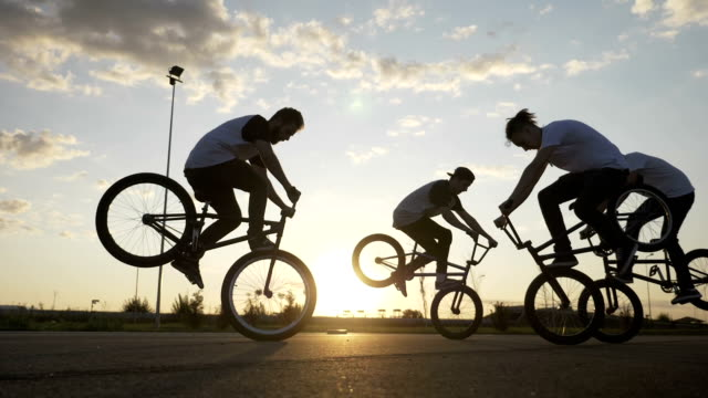 Cool young bikers team doing freestyle front wheelie trick outside with sunset in background