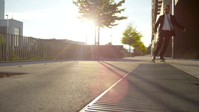 CLOSE UP: Cool young businessman skateboarding to work video