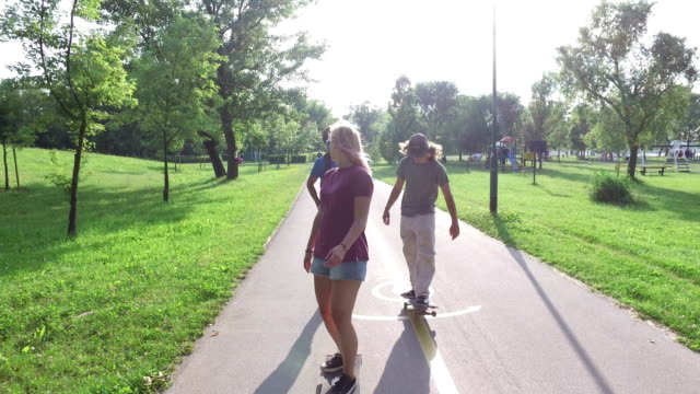 Cool young friends skateboarding on sunny day video