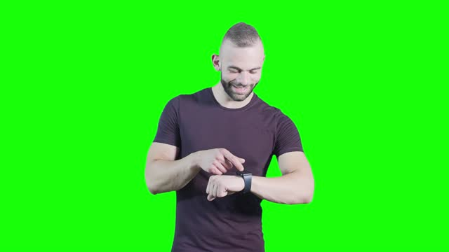 Cool young man using smartwatch against green background