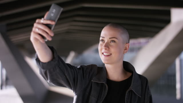 Cool young woman with buzz cut posing for selfie Cool young woman with buzz cut posing for selfie short hair stock videos & royalty-free footage