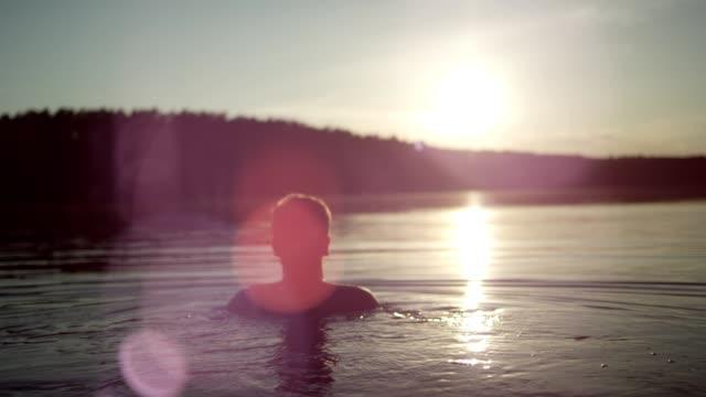 vidéos et rushes de rafraîchir dans le lac. coucher de soleil - prendre un bain