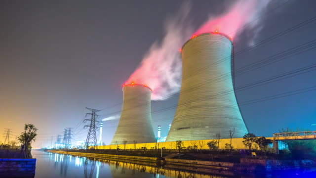 cooling tower with beautiful smoke near river at night. timelapse 4k