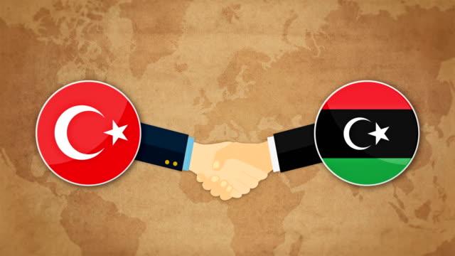 cooperazione tra turchia e libia. stretta di mano pronta con sfondo flag. animazione dei cartoni animati - libia video stock e b–roll