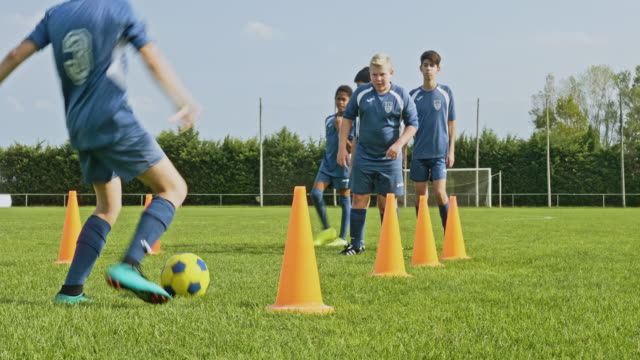 Coordinated Young Footballer Completing Dribbling Drill Focused preteen male footballer practicing dribbling around orange traffic cones on field with boys watching in background. practice drill stock videos & royalty-free footage