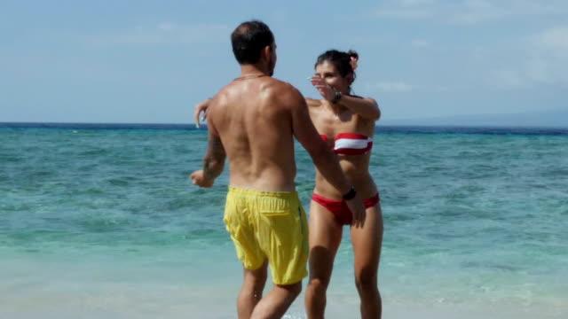 Coouple fooling around in the water in Gili Travangan beach