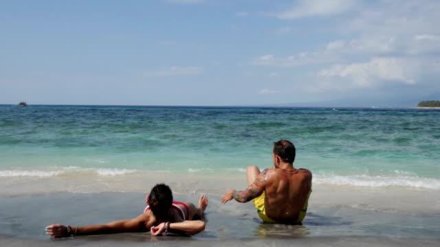 Coouple lying on the sand in Gili Travangan beach