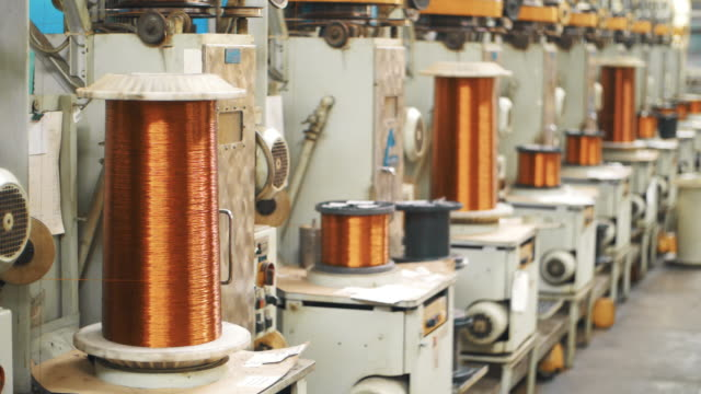 Copper wire winding on coils at factory. Bronze cable rolling on reels at plant