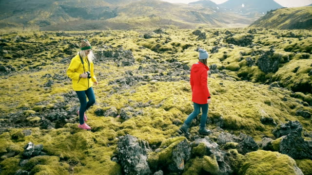 Copter flying around two woman on lava field in Iceland. Tourists with camera walking on the nature and taking photos