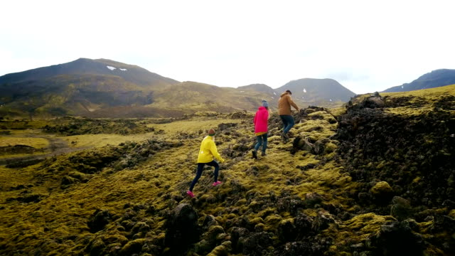 Copter flying over the group of tourists hiking on the mountain. Friend walking in the lava fields in Iceland