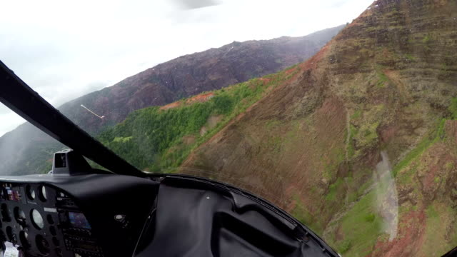 aerial: copter flying past the mountain cliffs and rocky walls in rainy hawaii - helikopter filmów i materiałów b-roll