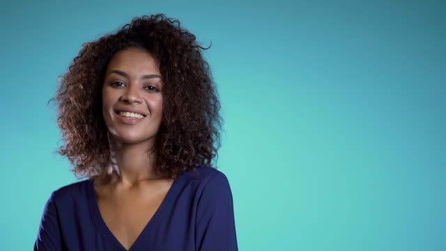 vídeos de stock e filmes b-roll de copy space. pretty african woman with afro hair in business clothing smiling to camera over blue wall background. cute mixed race girl's portrait. - afro americano