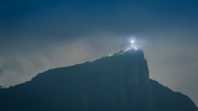 Corcovado Mountain in Rio de Janeiro by night, Brazil - Latin America. Corcovado Mountain in Rio de Janeiro by night, Brazil - Latin America. Time lapse with rolling clouds from low angle. Christ illuminated. cristo redentor stock videos & royalty-free footage