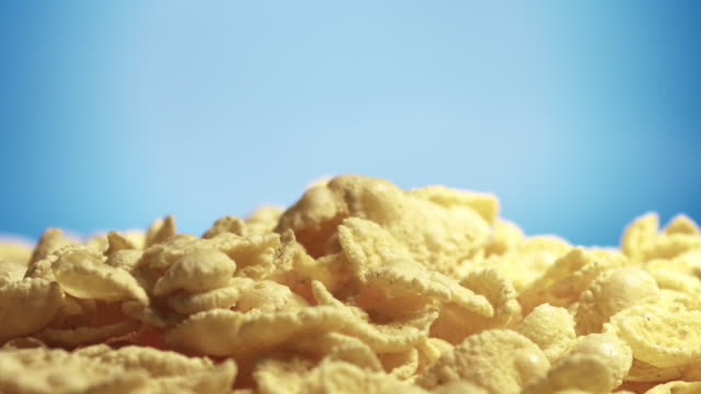Corn flakes falling on a heap on blue background video