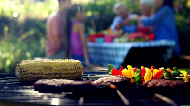 corn, sausages and meat being grilled on barbecue 4k - alla griglia video stock e b–roll