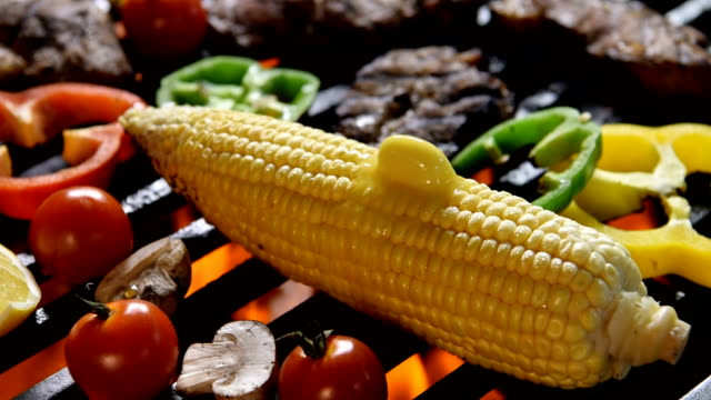 corn with melting butter on the flaming grill - grilling stock videos & royalty-free footage