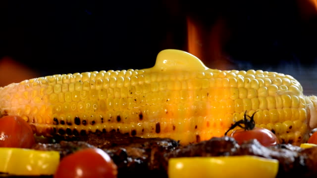 Corn with melting butter on the flaming grill video