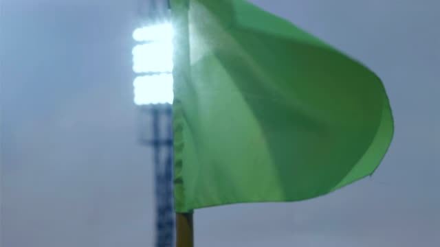Corner flag post blown by wind on soccer stadium at night, stadium lights in the background video