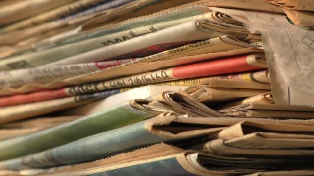 Corner view of newspaper stack on display.