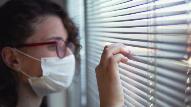 vídeos de stock e filmes b-roll de corona covid-19 virus protection. isolated sick woman with mask at hospital quarantine look through window blinds - isolado