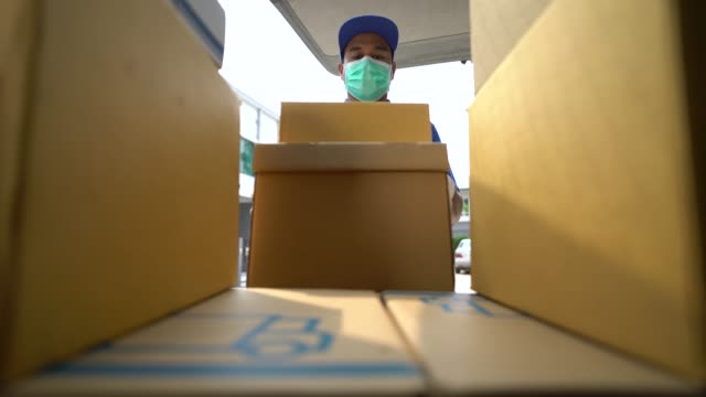 Corona Virus Concept. Asian blue delivery man wearing protection mask and medical rubber gloves mover unloads his cargo van prepare to send to customers. 4k resolution and slow motion shot.