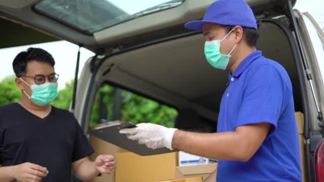 corona virus concept. asiatisk blå leverans man bär skyddsmask och medicinska gummihandskar skicka ett paket till kunden på innan leverera last. 4k upplösning och slow motion skott. - posttjänsteman bildbanksvideor och videomaterial från bakom kulisserna