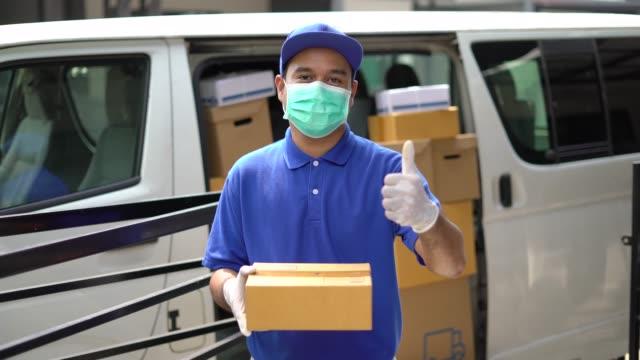 corona virus koncept, blue delivery stilig asiatisk man som håller paket kartong och tummen upp med skyddsmask och medicinska gummihandskar står framför van. slow motion skott. - posttjänsteman bildbanksvideor och videomaterial från bakom kulisserna